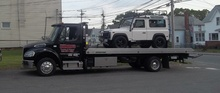 White jeep being towed